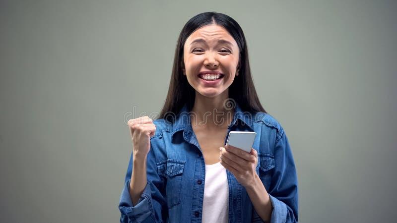 Glimlachende Aziatische vrouw die met smartphone ja gebaar, weggevertjewinnaar, geluk doen stock foto