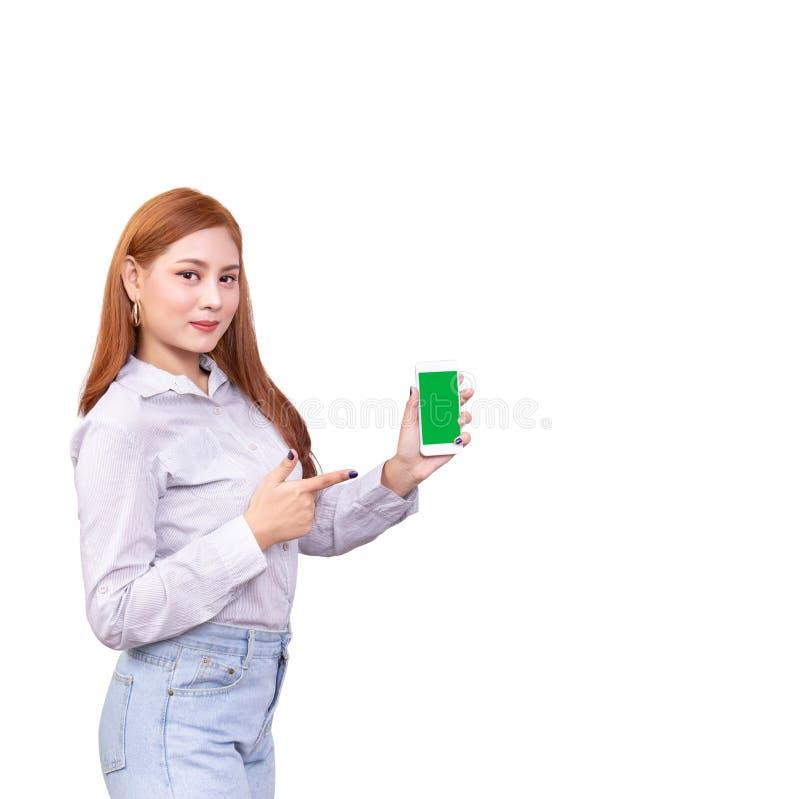 Glimlachende Aziatische vrouw die zich in toevallig overhemd bevinden die mobiele telefoon houden die en op smartphone richten op stock afbeelding