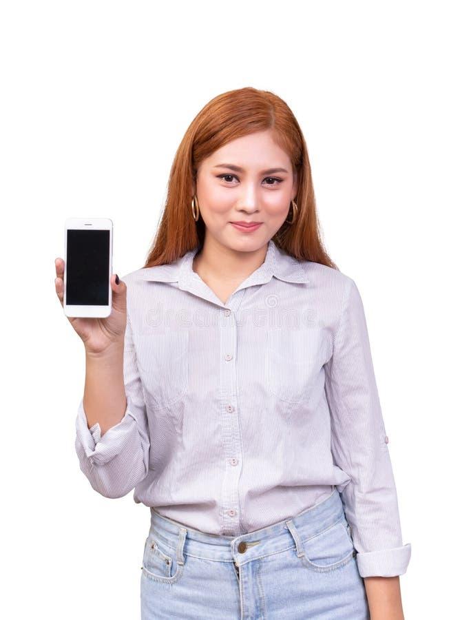 Glimlachende Aziatische vrouw die zich in toevallig overhemd bevinden die mobiele die telefoon houden op witte achtergrond met he royalty-vrije stock foto