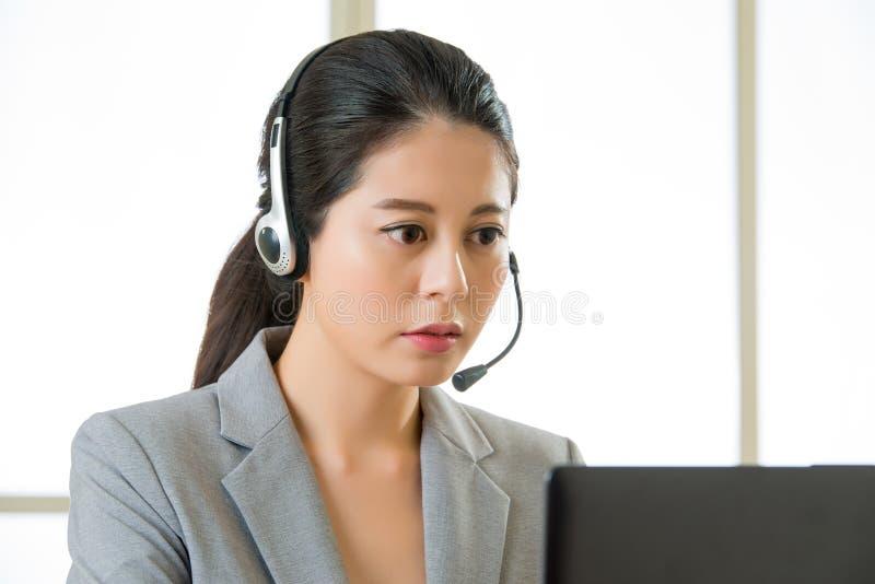 Glimlachende Aziatische vrouw met een hoofdtelefoon en het werken aan laptop stock foto