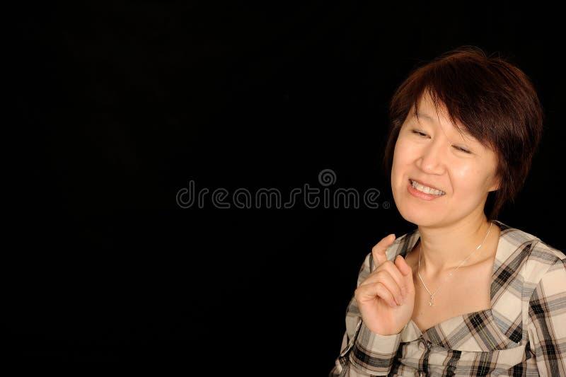 Glimlachende Aziatische vrouw op zwarte stock fotografie