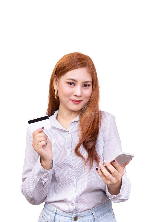 Glimlachende Aziatische vrouw in toevallig overhemd die mobiele telefoon houden en creditcard voor het winkelen tonen online terw royalty-vrije stock fotografie