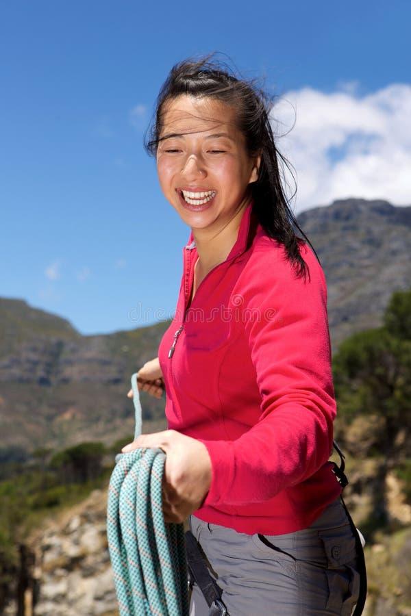 Glimlachende Aziatische vrouwelijke klimmer met kabel op berg royalty-vrije stock foto