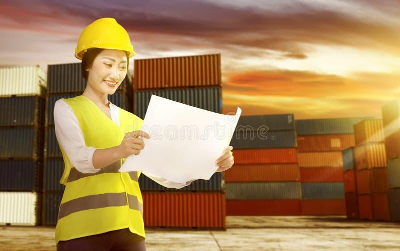 Glimlachende Aziatische vrouwelijke werknemer met veiligheidsvest en de blauwdruk van de bouwvakkerholding op het dok stock fotografie
