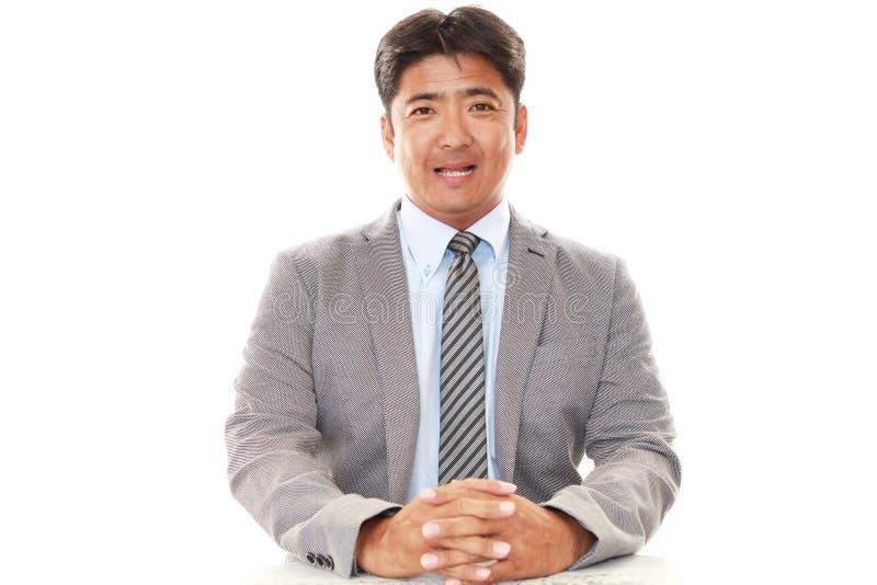 Glimlachende Aziatische zakenman stock afbeeldingen