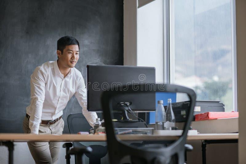 Glimlachende Aziatische zakenman die aan zijn computer in een bureau werken royalty-vrije stock foto