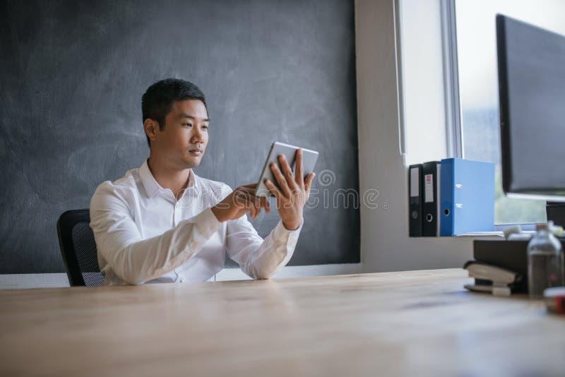 Glimlachende Aziatische zakenman die aan zijn tablet in een bureau werken stock fotografie