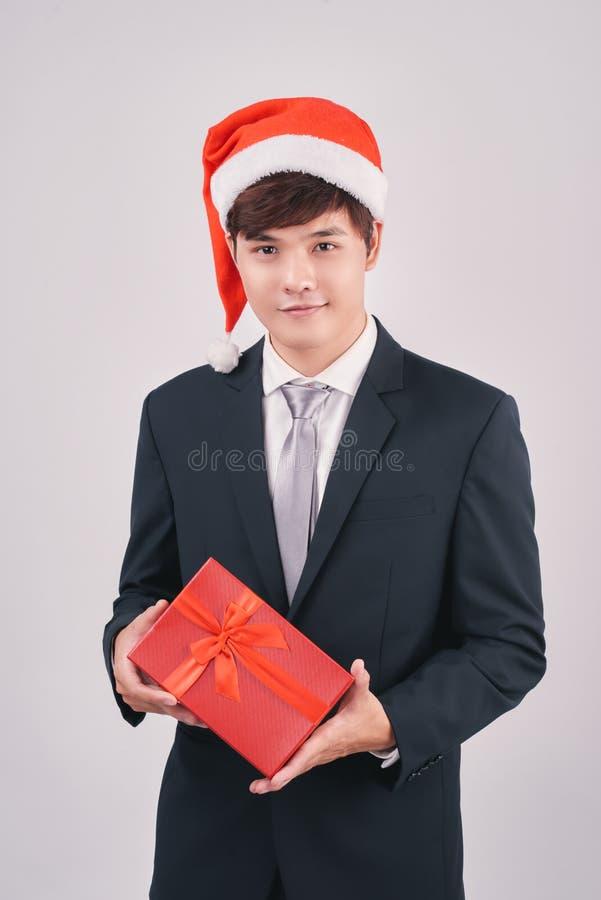 Glimlachende Aziatische zakenman die in geïsoleerd santahoed gift voorstellen stock fotografie