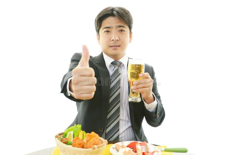 Glimlachende Aziatische zakenman met bier stock foto