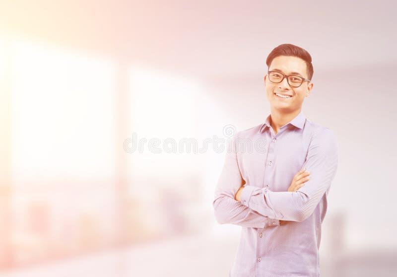 Glimlachende Aziatische zakenman in vaag zonovergoten bureau stock fotografie