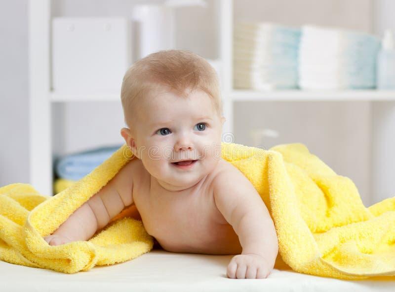 Glimlachende baby onder zachte handdoek Leuk kind die op bed na het baden in slaapkamer liggen stock fotografie