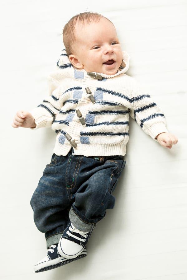 Glimlachende babyjongen in jeans en sweater die op bed liggen royalty-vrije stock afbeeldingen