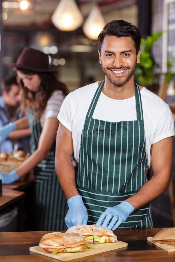 Glimlachende barista scherpe sandwich stock afbeelding