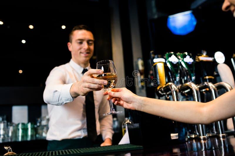 Glimlachende barman die glas witte wijn geven aan cliënt stock afbeelding