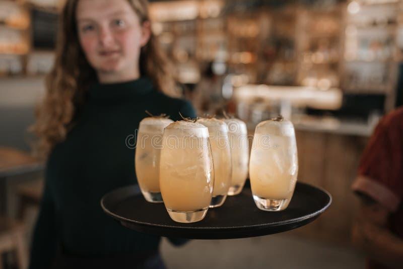 Glimlachende barserveerster die een dienblad van dranken houden stock foto