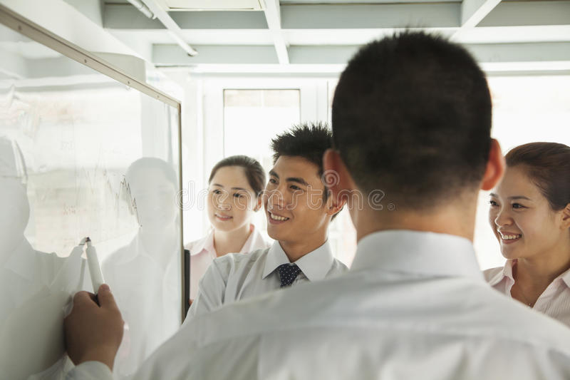 Glimlachende beambten die het diagram op whiteboard en het richten bekijken royalty-vrije stock fotografie