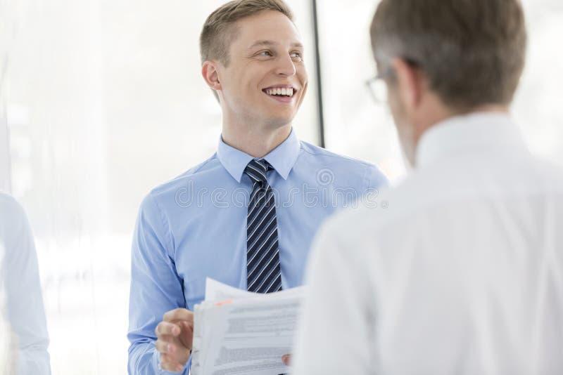 Glimlachende bedrijfscollega's die over document door muur op kantoor bespreken stock foto