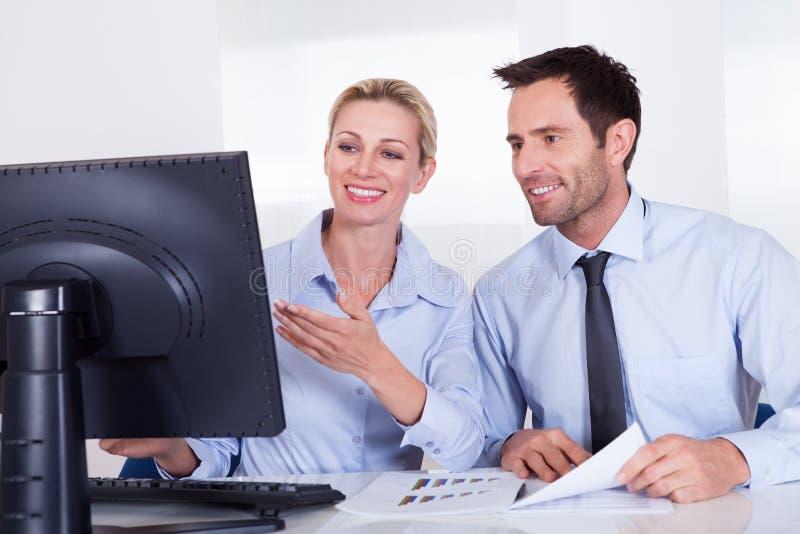 Glimlachende bedrijfscollega's die statistieken bespreken stock afbeeldingen