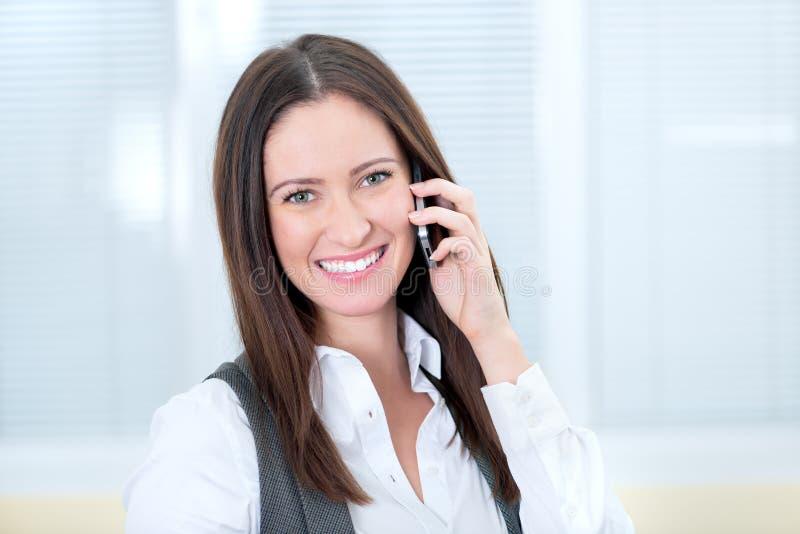 Glimlachende bedrijfsdame met mobiele telefoon stock foto's