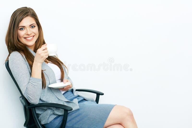 Glimlachende Bedrijfsdievrouw met de zitting van de koffiekop in offic wordt ontspannen stock fotografie