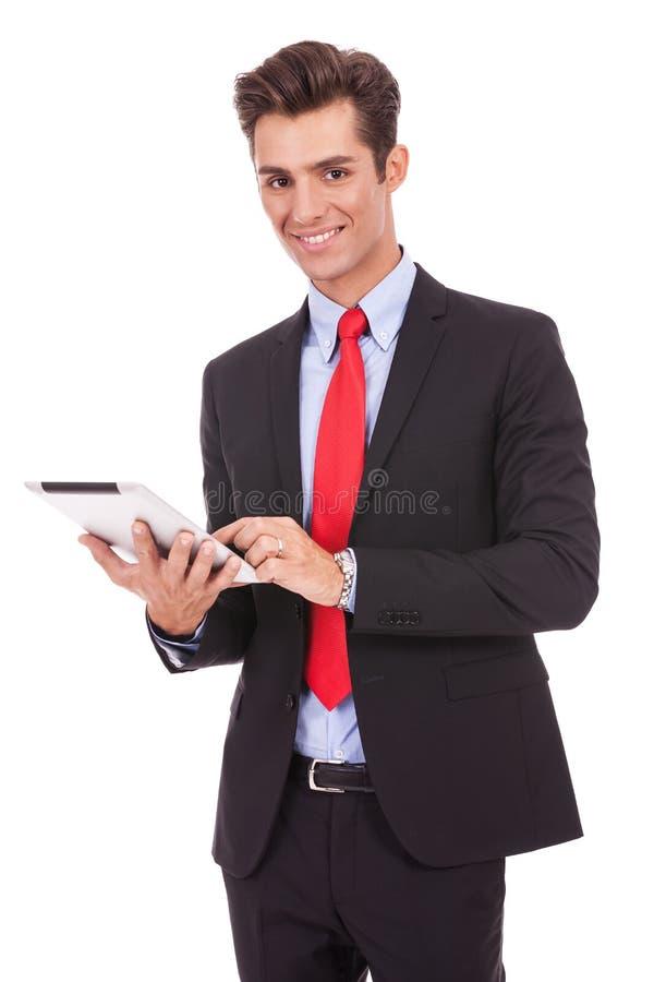 Glimlachende bedrijfsmens die zijn tabletstootkussen gebruikt stock foto's