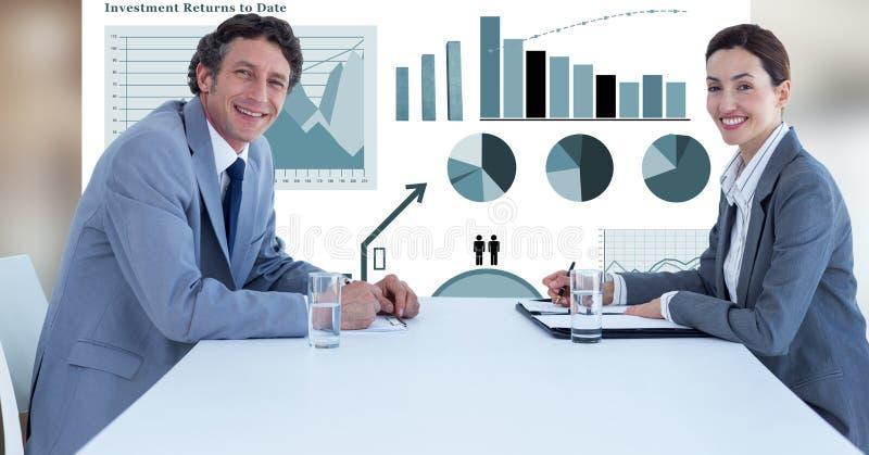 Glimlachende bedrijfsmensen bij bureau tegen grafieken royalty-vrije stock foto