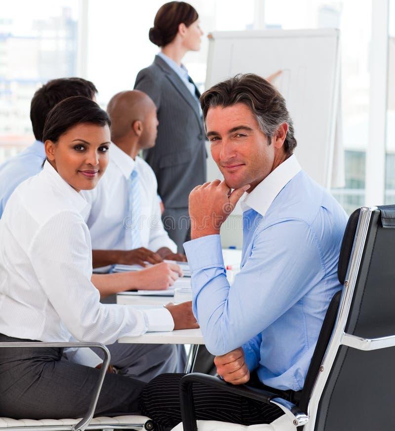 Glimlachende bedrijfsmensen bij een presentatie stock foto's