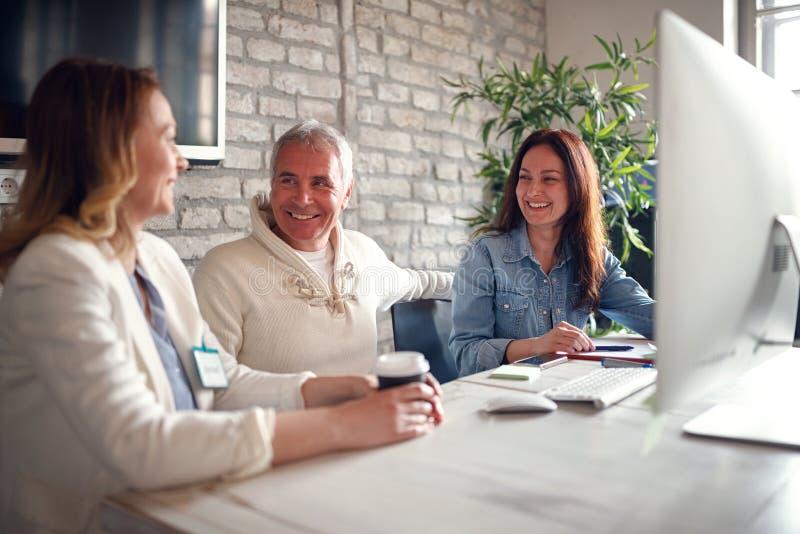 Glimlachende bedrijfsmensen die bij bureau aan computer samenwerken royalty-vrije stock foto's