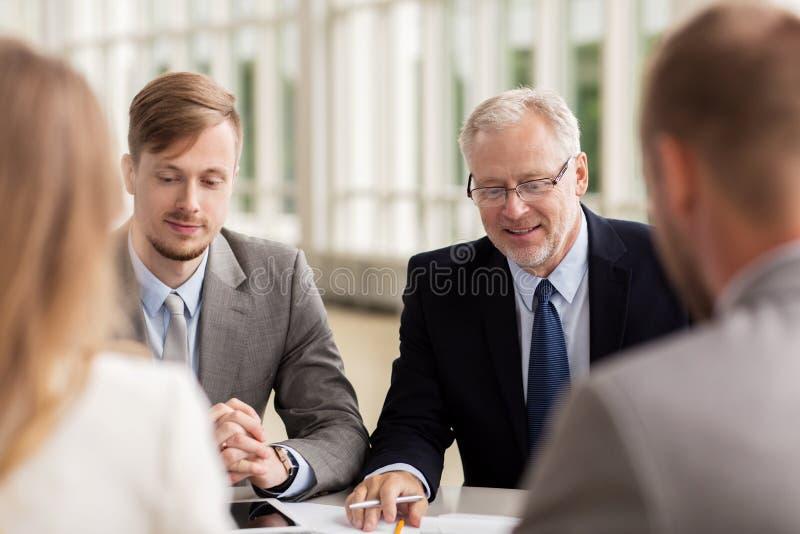 Glimlachende bedrijfsmensen die in bureau samenkomen stock afbeelding