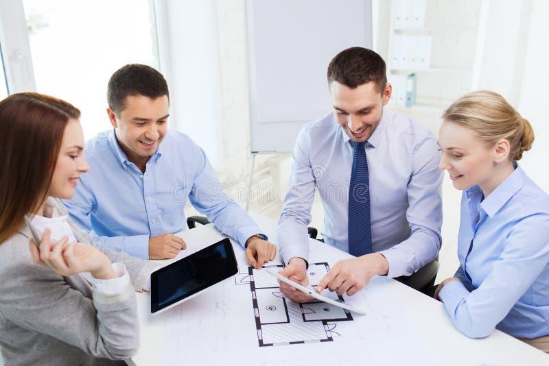 Glimlachende bedrijfsmensen die in bureau samenkomen royalty-vrije stock foto's