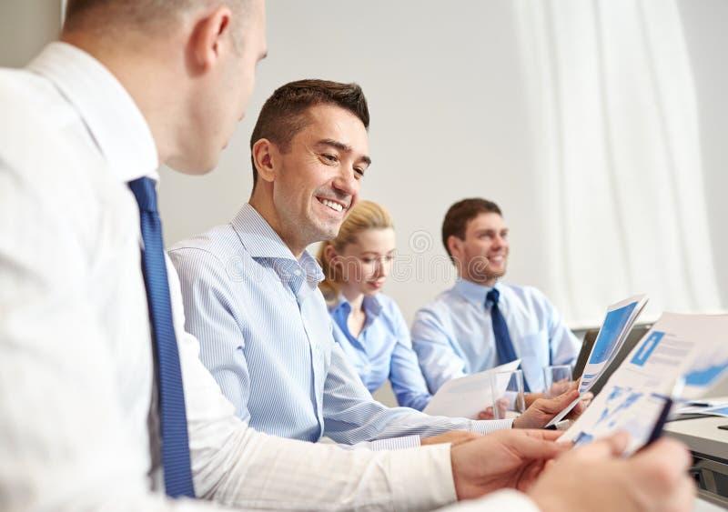 Glimlachende bedrijfsmensen die in bureau samenkomen royalty-vrije stock afbeelding