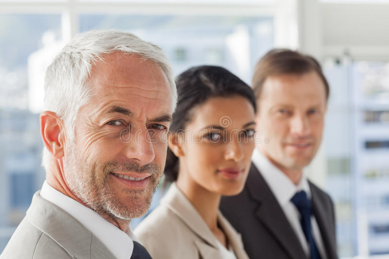 Glimlachende bedrijfsmensen die op dezelfde manier kijken stock foto