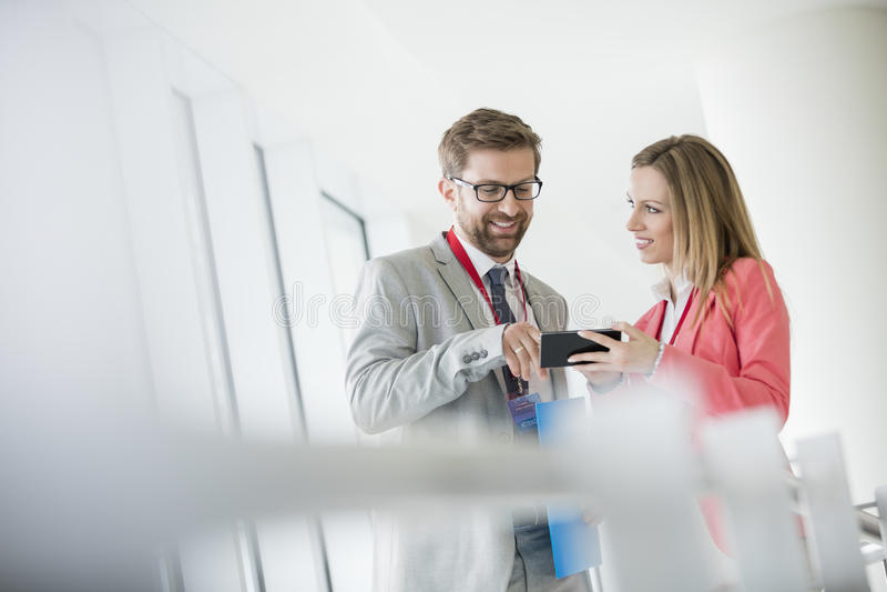 Glimlachende bedrijfsmensen die slimme telefoon in overeenkomstcentrum met behulp van royalty-vrije stock fotografie