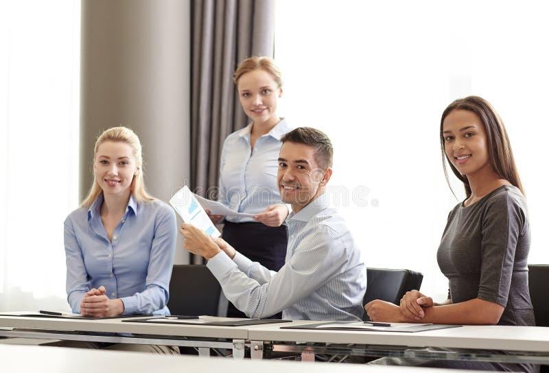 Glimlachende bedrijfsmensen met documenten in bureau stock fotografie