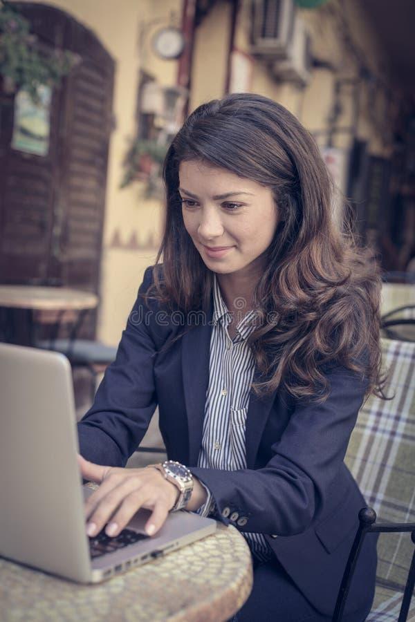 Glimlachende bedrijfsvrouw die, aan laptop buiten werken stock afbeeldingen