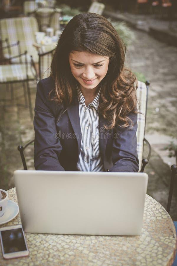 Glimlachende bedrijfsvrouw die aan laptop buiten werken royalty-vrije stock afbeeldingen
