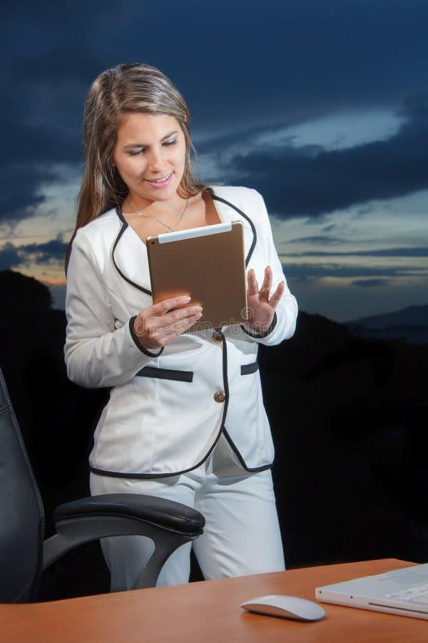 Glimlachende bedrijfsvrouw die digitale tabletpc met behulp van stock afbeelding