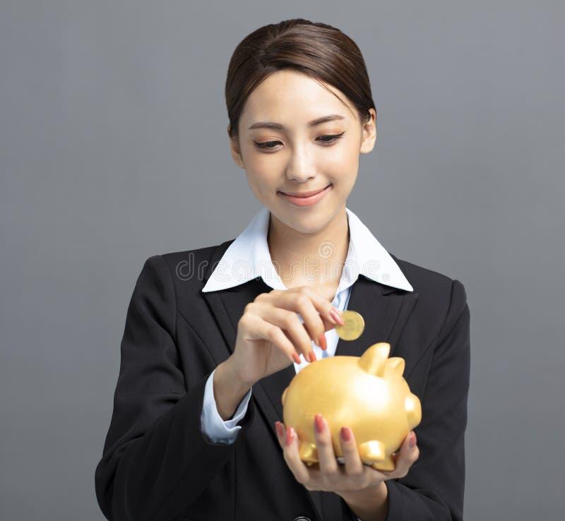 Glimlachende bedrijfsvrouw die geld zetten in spaarvarken royalty-vrije stock afbeeldingen