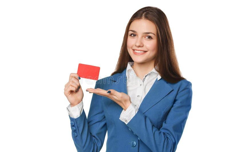 Glimlachende bedrijfsvrouw die lege creditcard in blauw die kostuum tonen, over witte achtergrond wordt geïsoleerd royalty-vrije stock foto