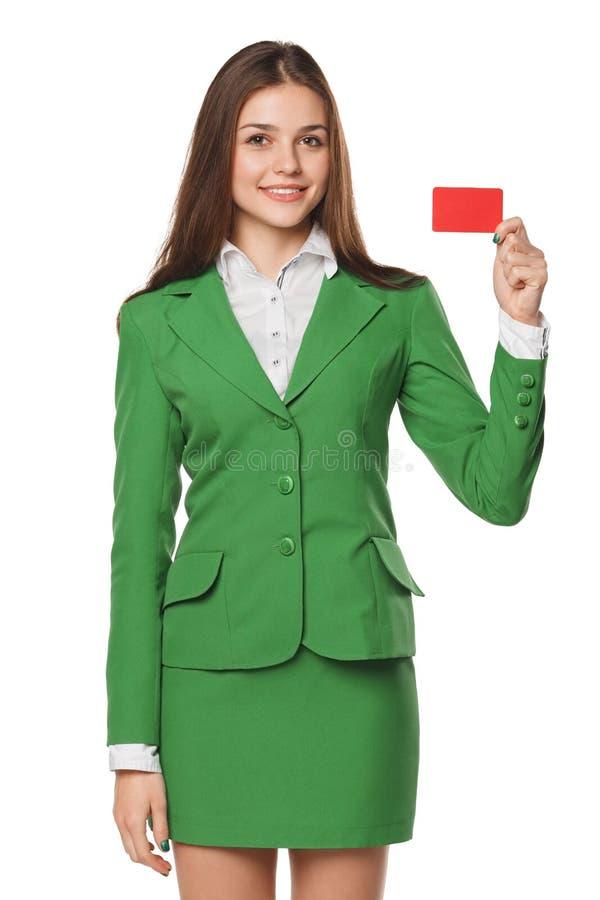 Glimlachende bedrijfsvrouw die lege creditcard in groen die kostuum tonen, over witte achtergrond wordt geïsoleerd stock afbeelding