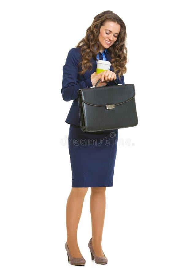Glimlachende bedrijfsvrouw die met aktentas en cofeekop tijd kijken royalty-vrije stock foto's