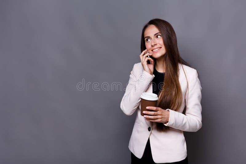 Glimlachende bedrijfsvrouw die mobiele telefoon spreken en koffie drinken op het werk royalty-vrije stock foto