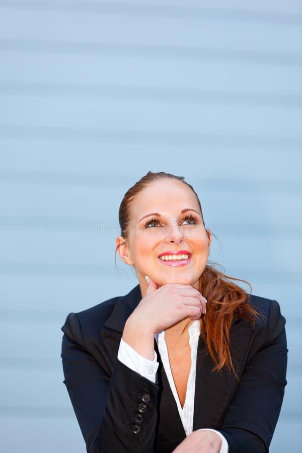 Glimlachende bedrijfsvrouw die omhoog exemplaar-ruimte bekijkt stock afbeelding