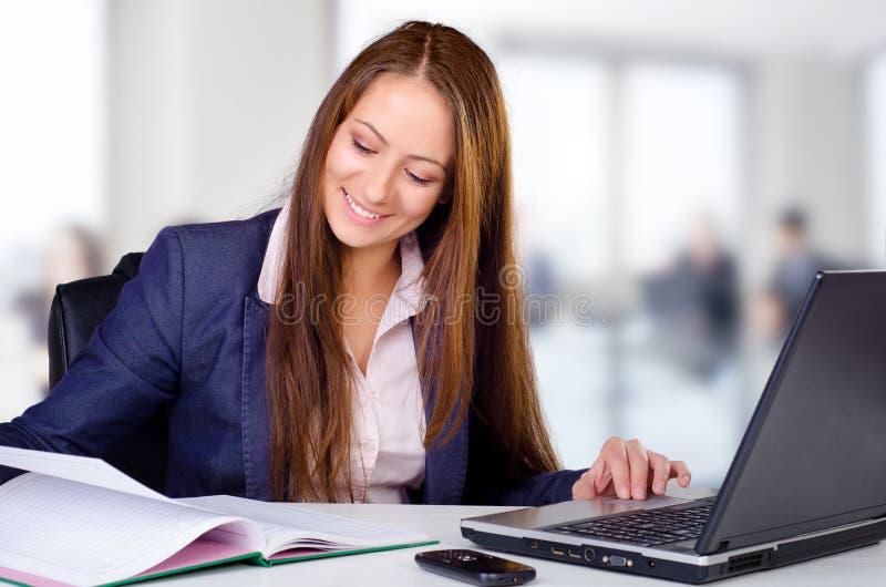 Glimlachende bedrijfsvrouw in haar bureau stock afbeeldingen