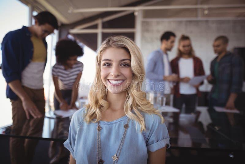 Glimlachende bedrijfsvrouw met creatief team op achtergrond stock afbeelding