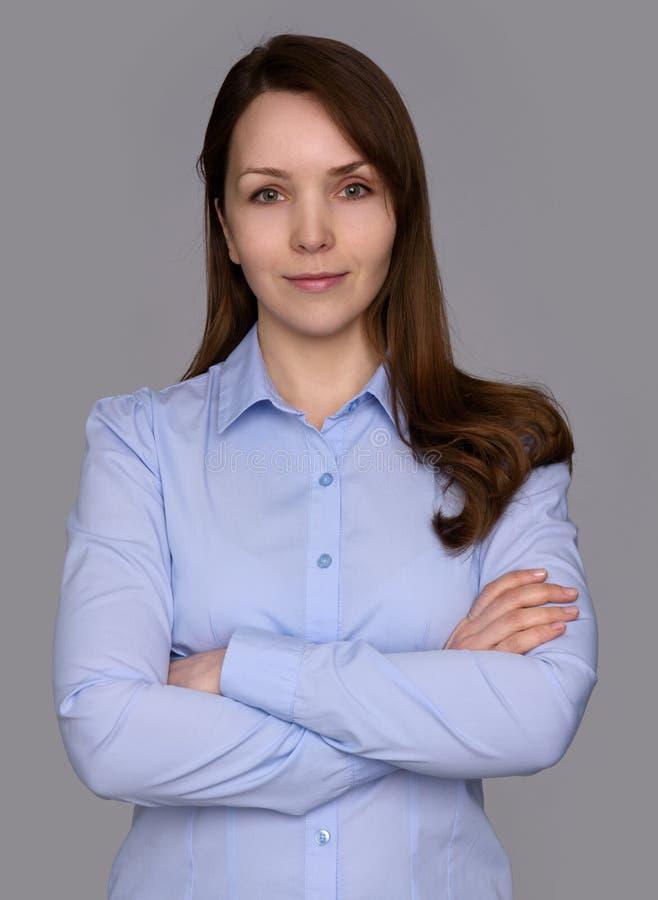 Glimlachende bedrijfsvrouw met gekruiste wapens stock afbeeldingen