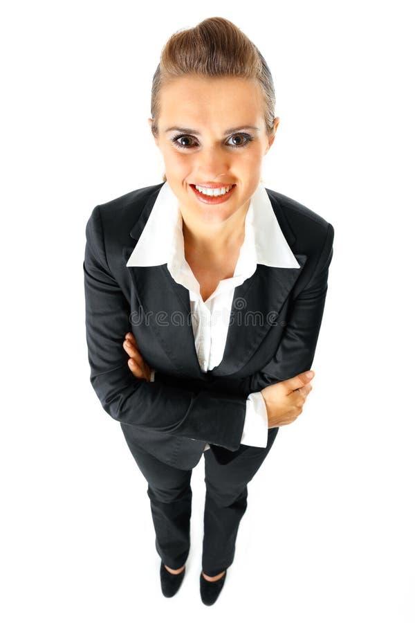 Glimlachende bedrijfsvrouw met gekruiste wapens op borst stock foto