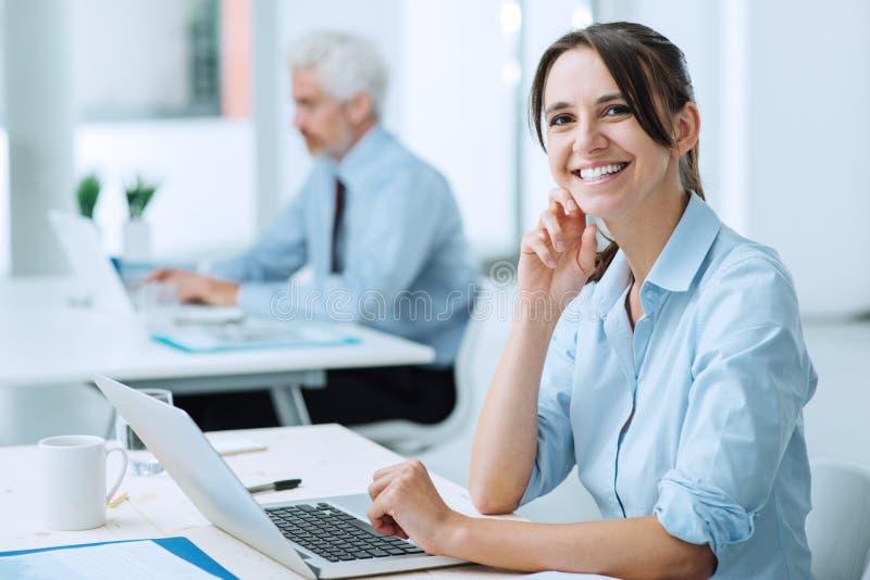 Glimlachende bedrijfsvrouw op het werk stock fotografie