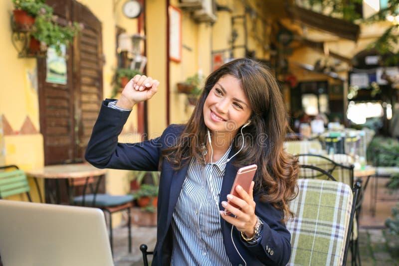 Glimlachende bedrijfsvrouw op koffiepauze het luisteren muziek, die sm gebruiken royalty-vrije stock fotografie