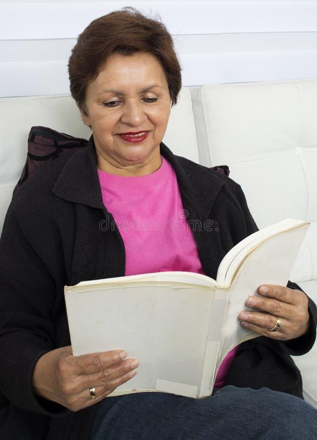 Glimlachende bejaarde dame die een boek lezen terwijl het zitten stock foto